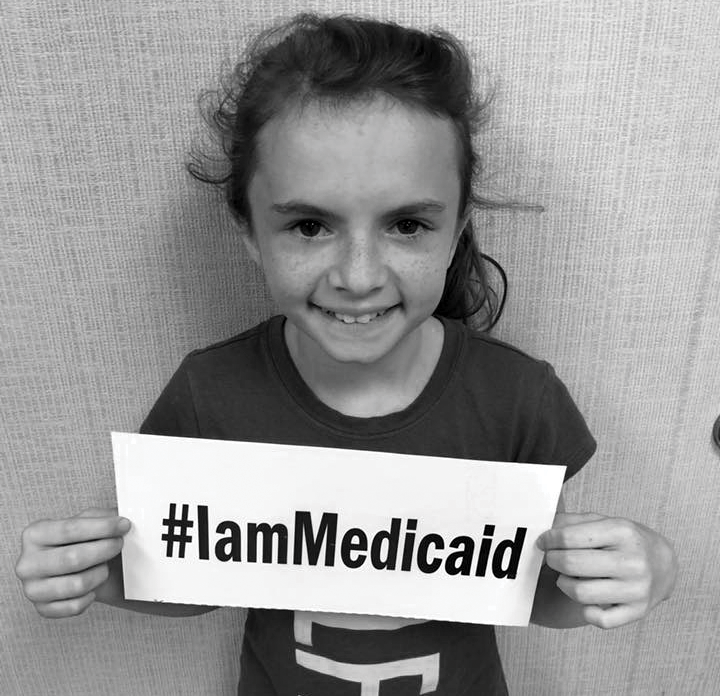 Young girl holding sign reading #IamMedicaid